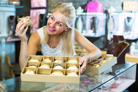 friendly smiling young female jeweler showing fashion bracelets in bijouterie boutique  Stock Photo