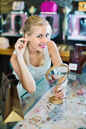 Portrait of young charming cheerful woman choosing earrings in shop with bijouterie
