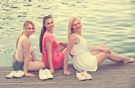 portrait of three cheerful young women resting together on esplanade in european city