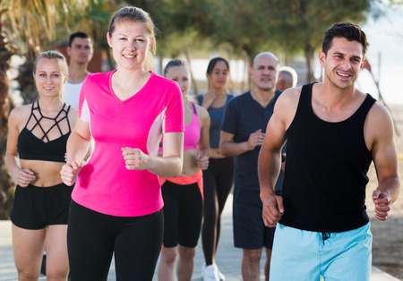 Active smiling people during running training in daytime