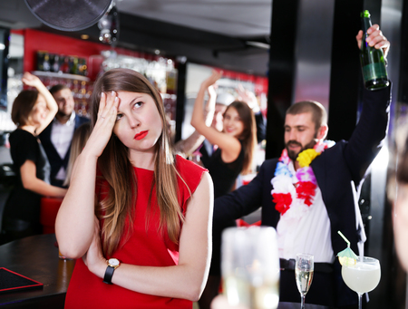 Offended young woman on background with drunk man on party at the nightclub