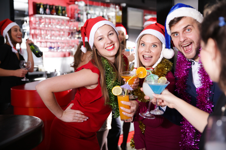 Cheerful guy with two girls funning and toasting drinks on new year eve party in bar