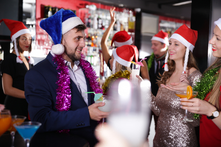 Young man and two women with cocktails in Santa hats celebrating at nightclub