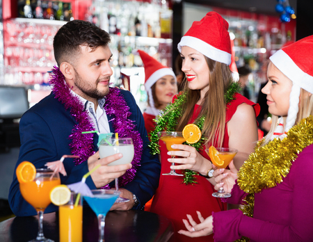 Young cheerful man and two women with cocktails in Santa hats celebrating at nightclub