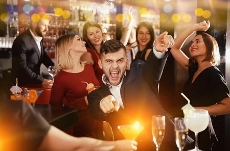 Cheerful guy expressively dancing partying in bar