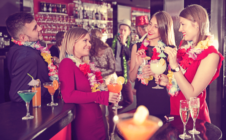 Happy young colleagues enjoying corporate event in Hawaiian style in bar Stock Photo