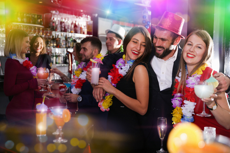 Young man and two women with cocktails having fun on Hawaiian party at nightclub Stock Photo