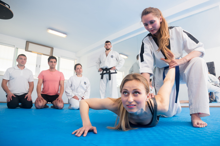 Young girl in a taekwondo training teaches new tricks of defense