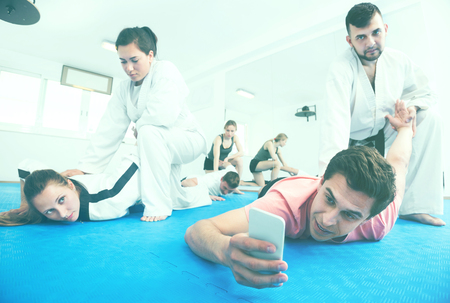 Young adults taking photos while practicing a new taekwondo holds