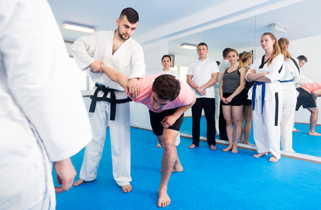 Positive young male coach explaining painful hold to adults in taekwondo class