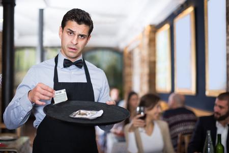 Amazed waiter holds money for order in a restaurant 版權商用圖片
