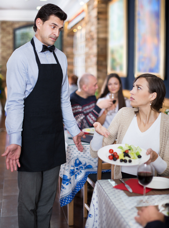 Adult couple expressing dissatisfaction with the waiter about food