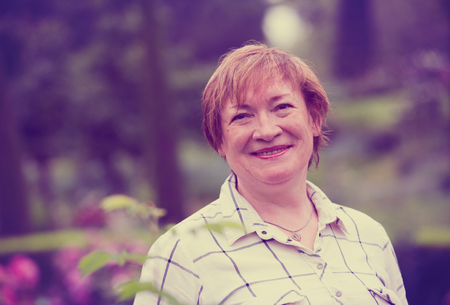 Portrait of cheerful retiree woman standing outdoors in fine weather Stock Photo