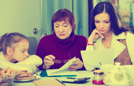 Two women with little girl faced financials troubless, sitting at table with bills Фото со стока