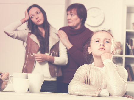 Upset little girl sitting at home table while grandmother calming her mother after quarrel