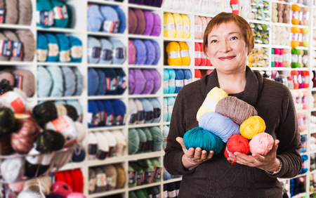Portrait of positive elderly woman holding colorful knitting yarns on store shelves background Stock Photo