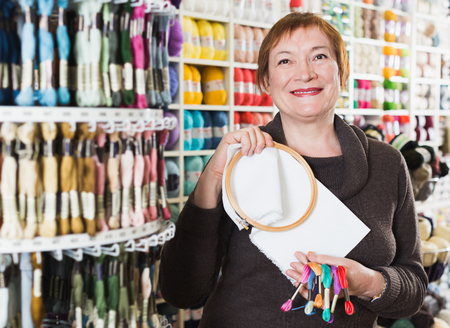 Smiling mature woman standing with accessories for embroidery in needlework shop