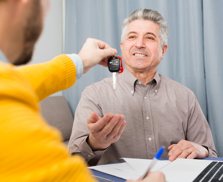 Mature man and manager signed contract car lease at home and hand over keys Stock Photo