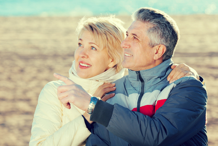 Mature couple walks outdoors and point by hand to interesting objects Stock Photo