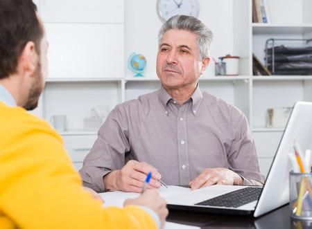 Man and mature bank employee discuss and sign credit agreement in office Stock Photo