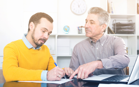 Young man and bank employee discuss and sign credit agreement in office Stock Photo