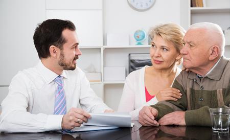 Rijpe vrouw en oudere man die leningsovereenkomst met de manager van de kredietafdeling ondertekenen
