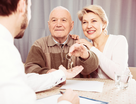 Elderly man and woman hand over an apartment for rent at agreement and give keys Stock Photo