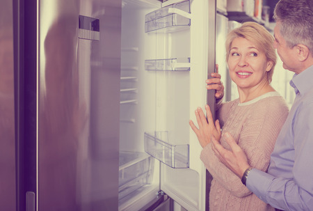 Nice mature married couple choose for themselves refrigerator in center of household appliances Stock Photo