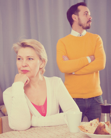 Son defends his position before mature mother at home