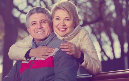 Souriant mature couple marié assis sur un banc de parc sur une journée ensoleillée Banque d'images - 92930098