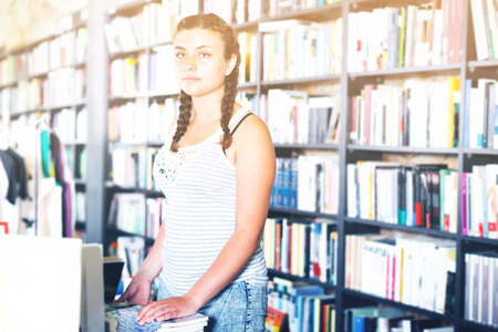 Young pretty female customer is choosing new book for buying in bookstore