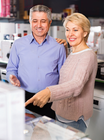 Adult glad cheerful married couple in store looking at and choose home appliances for your home