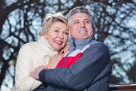 Smiling mature couple relaxing in park sitting on bench. Focus on man