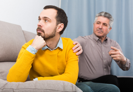 Adult Vater und Sohn diskutieren Probleme in der Familie zu Hause auf der Couch Standard-Bild - 92930471