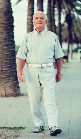 Portrait of mature man walking in the park at weekend