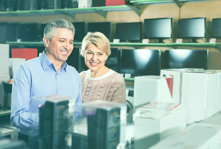Adult cheerful smiling married couple in store looking at and choose home appliances for your home Stock Photo