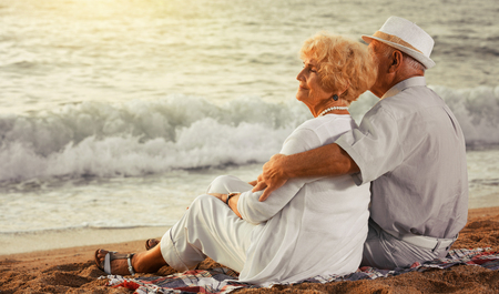mature man and woman sitting back and hugging on the sea shore  Reklamní fotografie