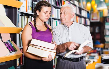 grootvader met meisje leest literatuur in boekhandel.