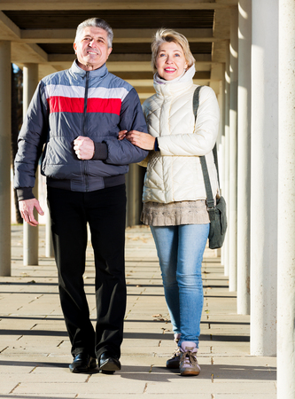 Happy mature couple goes for walk between concrete pillars on sunny day Stock Photo