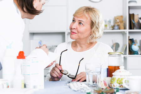 Doctor explains the mature woman how to take medicine for successful treatment