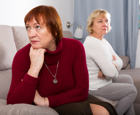 Senior woman sitting separately offended after quarrel with her female friend
