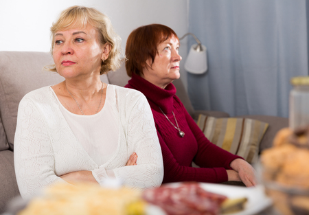 Frustrated elderly woman sitting separately having problems in relationship with female friend