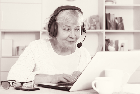 Buxom woman of an age sits in front of table with laptop in headphones with microphone