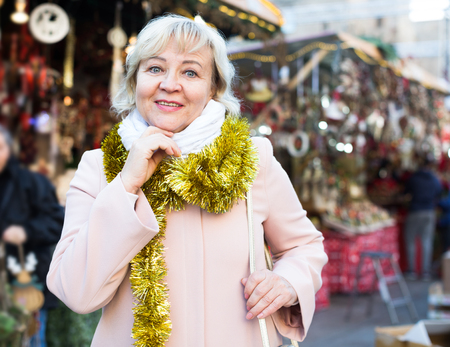 tourist mature female in garland on neck on Christmas Fair