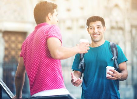 남자 친구들은 도시에서 걷고있는 시간에 커피를 마시 며 이야기하고 있습니다.