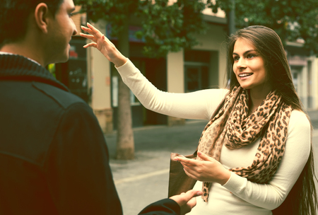 Positive russian brunette showing direction to Indian guy at the street Stock Photo