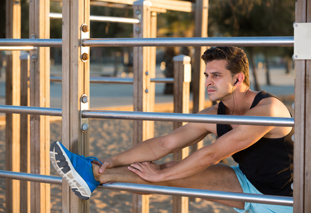 Male athlete stretching legs on outdoor fitness station after strength training on beach