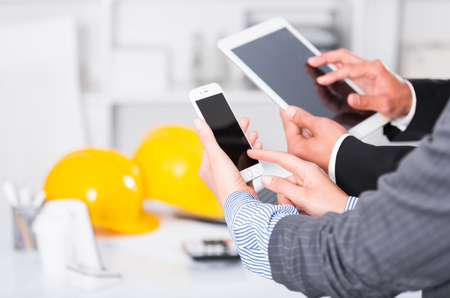 Business team holding and using phone and tablet at workplace in office