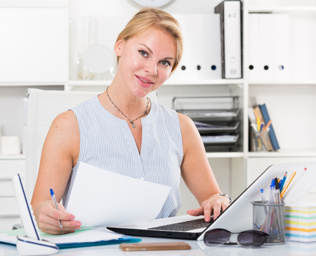 portrait of young spanish  business woman  writing and working with laptop in office  Stock Photo