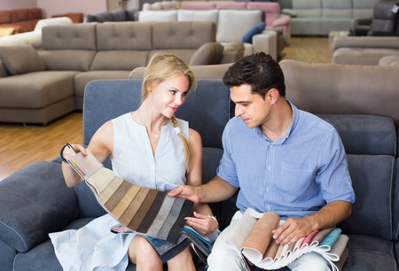 Happy male and wife choosing colors for new sofa in  furniture shop  Stock Photo
